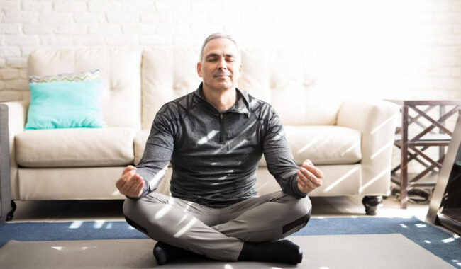 Portrait of healthy mature man sitting crossed legged on fitness mat and meditating in lotus yoga pose at home